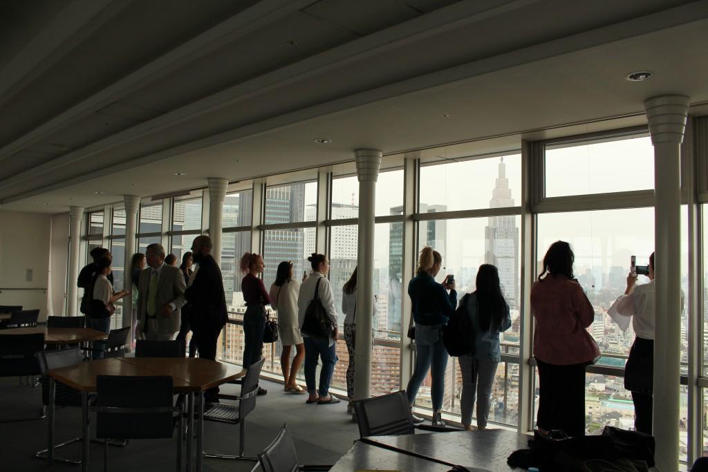 校舎より東京の景観を眺める学生